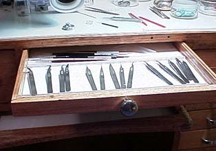 Escapement tweezers in table
